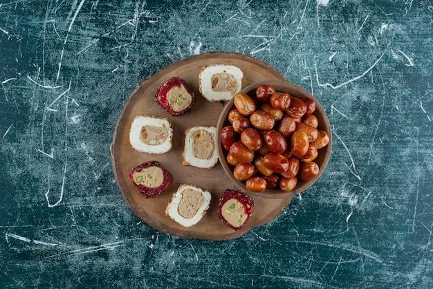 Bol de dattes séchées et délices sucrés sur morceau de bois.