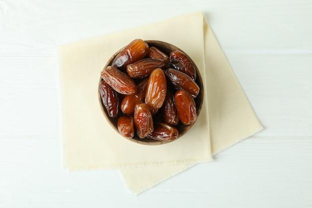Bol avec dattes séchées sur serviette de cuisine sur table en bois blanc