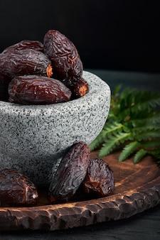 Bol de dattes séchées sur table en bois foncé