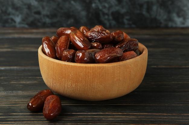 Bol avec dattes séchées sur table en bois