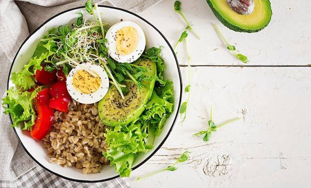 Bol à déjeuner avec flocons d'avoine, paprika, avocat, laitue, micro-légumes et œuf à la coque.