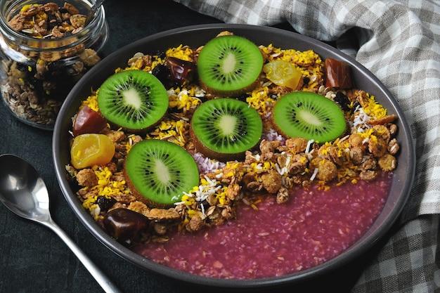 Bol à déjeuner avec smoothie à l'açai, flocons d'avoine, granola et fruits.