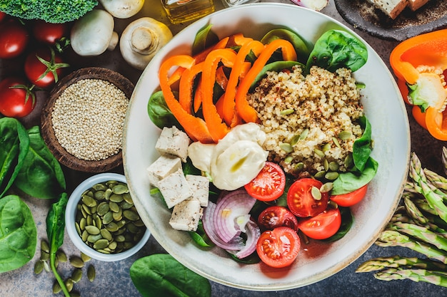 Bol à déjeuner végétalien avec quinoa, brocoli, houmous et champignons.