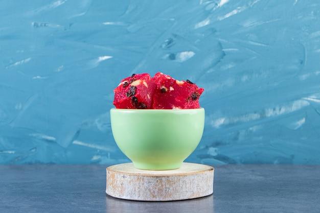 Un bol de délices turcs sur une planche sur la surface en marbre