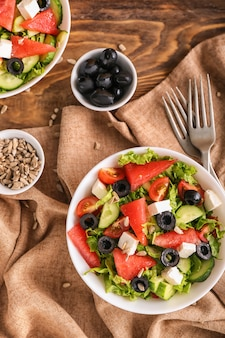Bol avec une délicieuse salade de pastèque sur table, vue de dessus