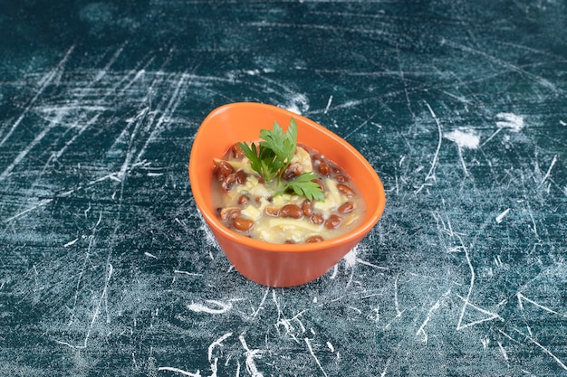 Bol de délicieuse soupe avec des pâtes et des haricots sur fond bleu. photo de haute qualité