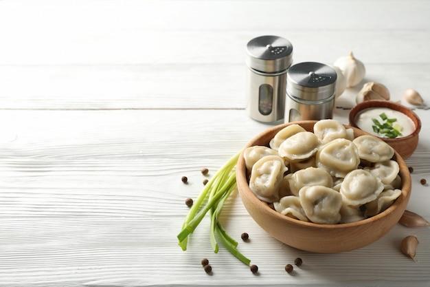 Bol avec de délicieuses boulettes et épices sur fond de bois, close up
