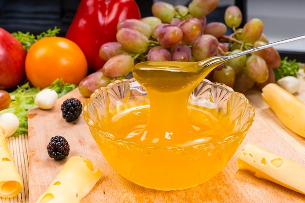 Bol de délicieux miel doré frais arrosé d'une cuillère servie sur une table de buffet avec un assortiment de fromages, de mûres, de tomates et de raisins frais