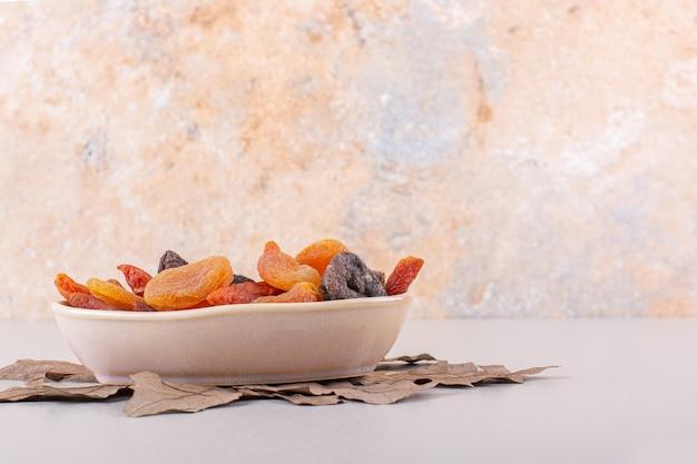 Bol de divers fruits biologiques avec feuille sèche sur fond blanc. photo de haute qualité