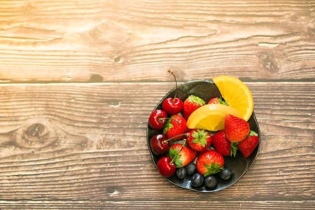 Bol de divers fruits sur une table en bois