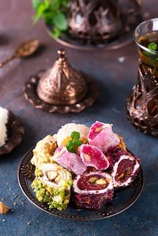 Bol avec divers morceaux de délice turc lokum et thé noir à la menthe