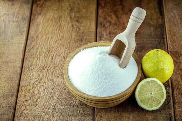 Bol avec du bicarbonate de soude et des agrumes comme le citron ou l'orange autour.
