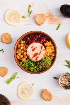 Bol avec du riz et des légumes entourés de citron et de pain sur un fond texturé blanc
