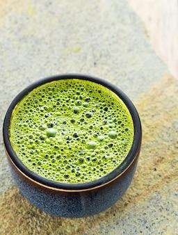 Bol avec du thé vert matcha avec de la mousse sur une surface en pierre grise