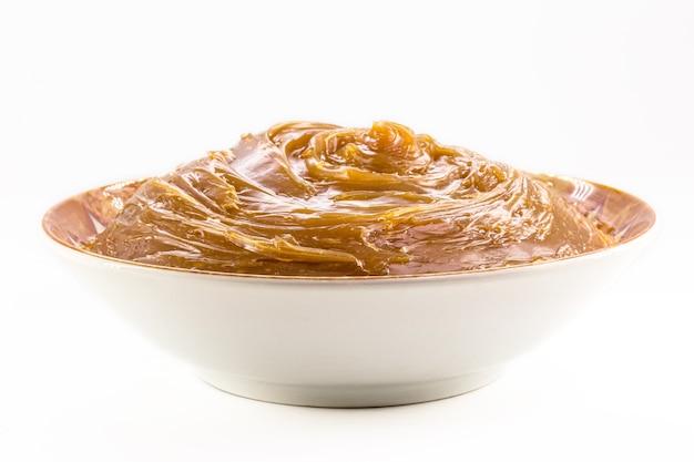 Bol avec dulce de leche fait maison, crème condensée ou caramel pâteux, fond blanc isolé.