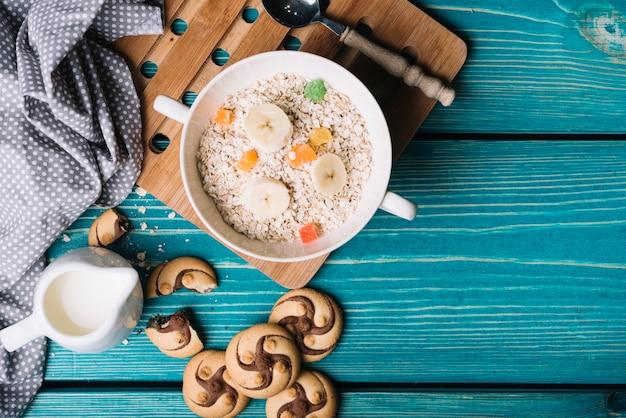 Bol de farine d'avoine avec garnitures de fruits et biscuits