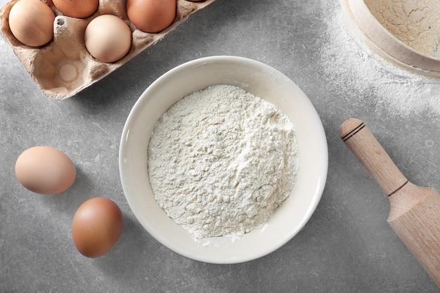 Bol avec farine blanche, œufs et rouleau à pâtisserie sur table de cuisine
