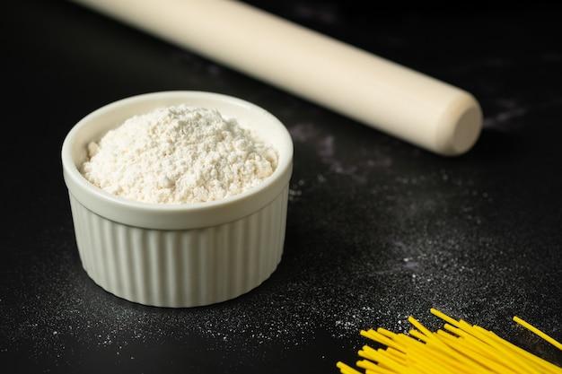 Bol de farine sur fond sombre farine dans une tasse en céramique tasse d'amidon avec espace de copie.