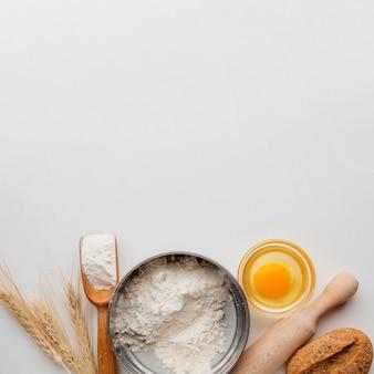 Bol à farine avec oeuf et rouleau à pâtisserie