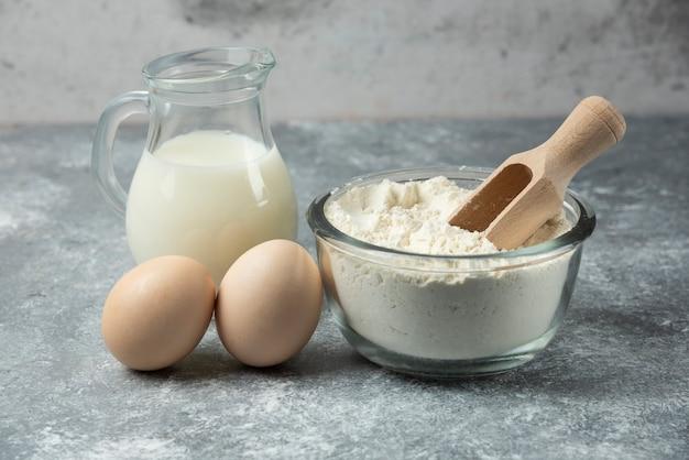 Bol de farine, œufs crus et lait sur table en marbre.
