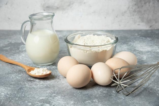 Bol de farine, œufs et lait sur marbre.