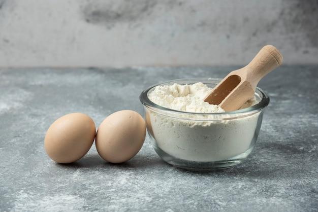 Bol de farine et œufs sur table en marbre.