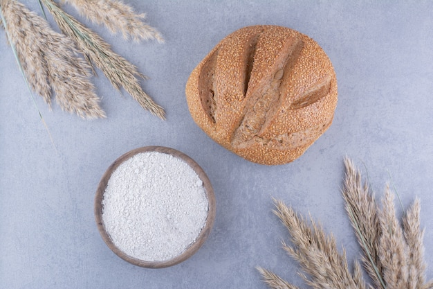 Bol de farine de pain et de tiges d'herbe de plumes séchées sur la surface en marbre