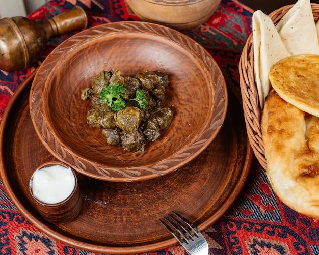 Un bol de feuilles de vigne dolma servi avec du yaourt