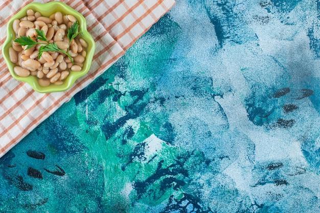 Un bol de fèves au lard appétissantes sur un torchon, sur la table bleue.