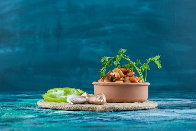 Bol de fèves au lard avec du persil à côté de l'ail et du poivre sur un dessous de plat, sur la table bleue.