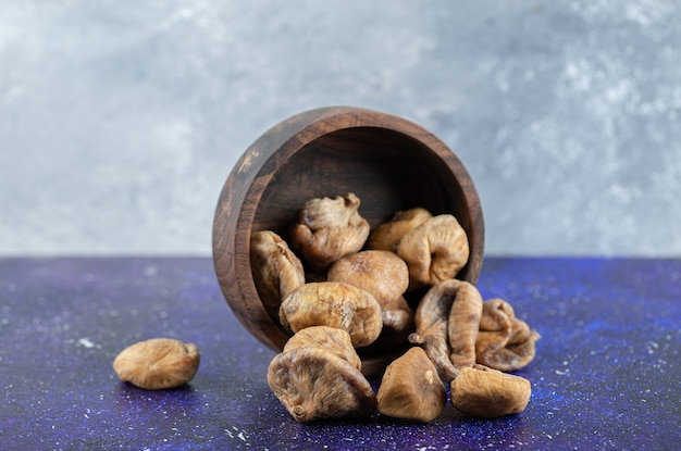 Bol de figues séchées sur table bleue.