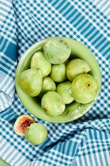 Un bol de figues vertes juteuses et de tranches de figue sur une nappe bleue.