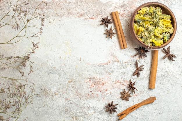 Un bol de fleurs séchées jaune vif et de bâtons de cannelle et d'anis sur marbre