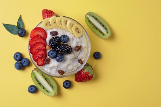 Bol de flocons d'avoine, fraises, myrtilles, kiwis et mûres sur fond jaune