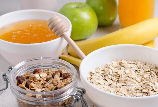 Bol de flocons d'avoine et raisins secs. miel, bananes, pommes vertes, noix