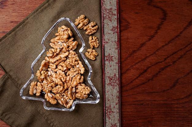 Bol en forme d'arbre de noël rempli de noix. vue de dessus. espace de copie.