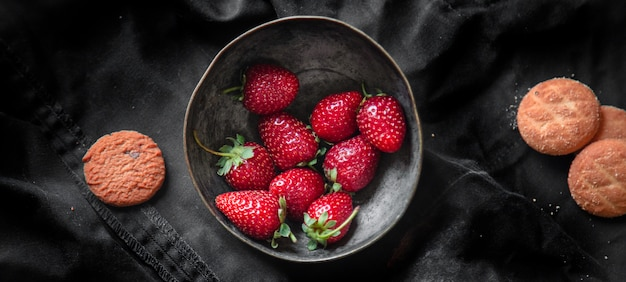 Bol de fraises et biscuits sur un tapis noir, vue de dessus.