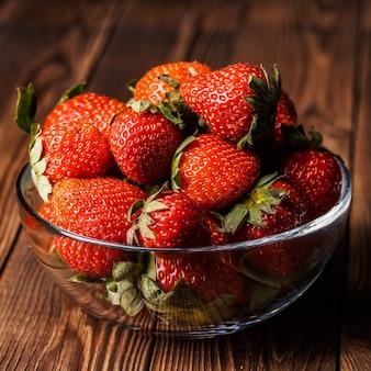Bol avec des fraises fraîches sur table en bois