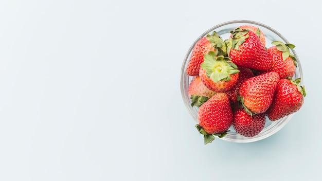 Bol de fraises juteuses sur fond blanc