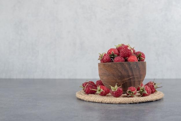 Bol de framboises rouges savoureuses sur fond de marbre. photo de haute qualité