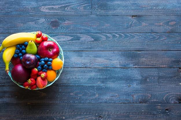 Bol de fruits frais avec banane, pomme, fraises, abricots, myrtilles, prunes, grains entiers, fourchettes, vue de dessus