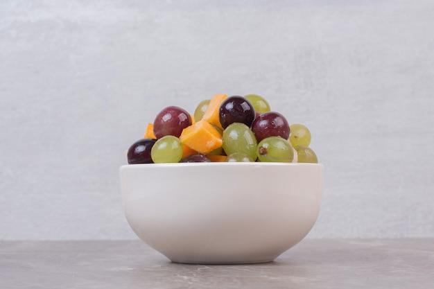 Bol de fruits mélangés sur table en marbre.