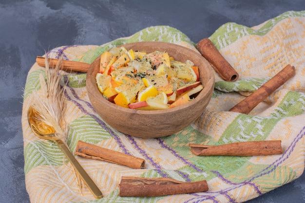 Bol de fruits en tranches avec de la cannelle et un chiffon sur bleu.