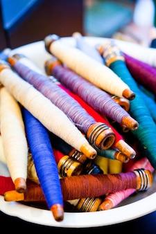 Bol de fuseaux plein de fils multicolores