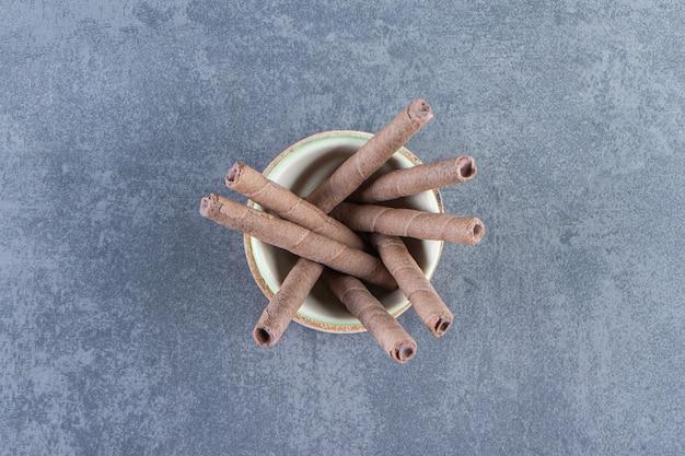 Un bol de gaufrettes au chocolat roule sur une planche , sur le fond de marbre.