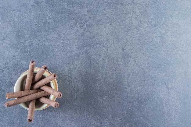 Un bol de gaufrettes au chocolat roule sur une planche sur la surface en marbre