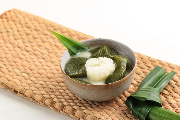 Un bol de gelée d'herbe jaune ou de cincau hijau, servi avec du lait de coco glacé et du sucre de palme liquide avec des feuilles de pandan. populaire en indonésien pour buka puasa (petit déjeuner) tajil ramadan