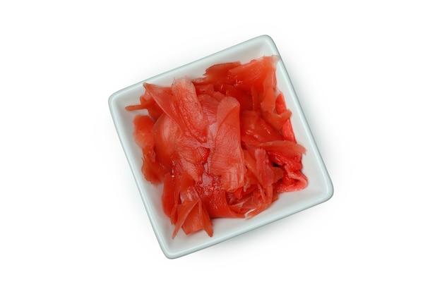 Bol avec gingembre mariné rouge isolé sur surface blanche