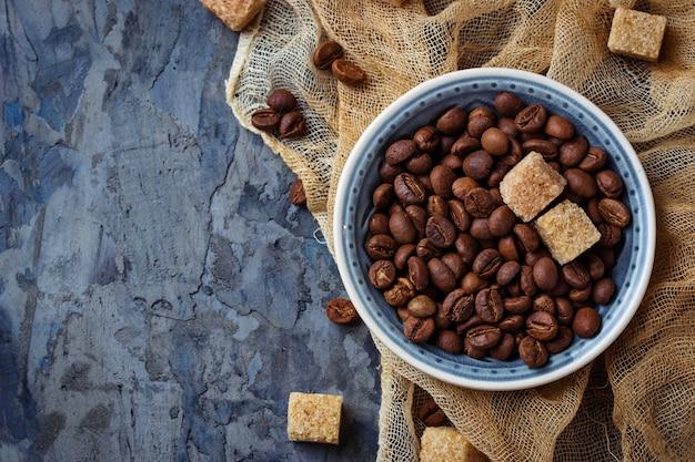 Bol de grains de café et de sucre de canne brun. mise au point sélective