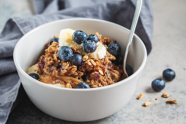 Bol granola fait maison avec bleuets, banane et miel.